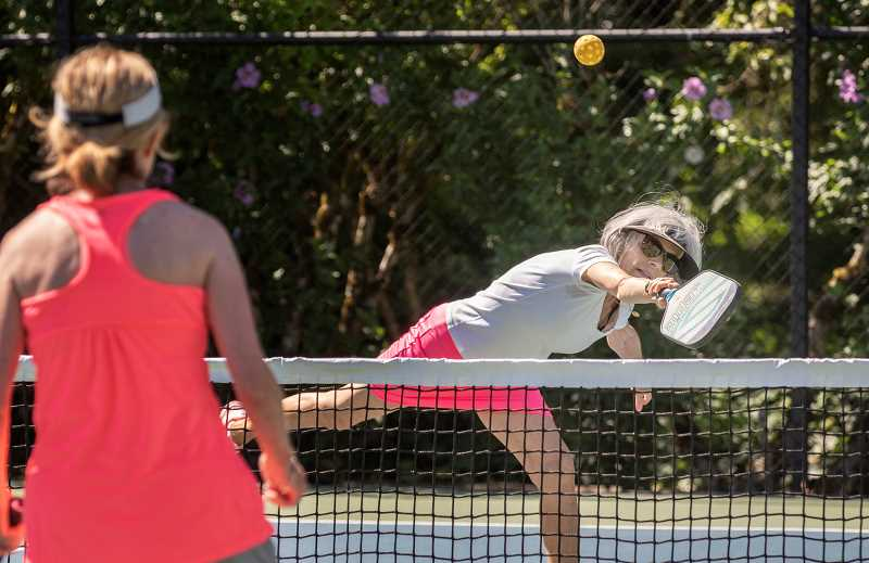 PMG PHOTO: JONATHAN HOUSE - Susan Gilbert stretches for the ball during open play with the Lake Oswego Pickleball Club.