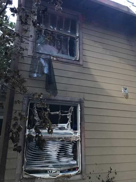 COURTESY TUALATIN VALLEY FIRE & RESCUE - TVF&R firefighters quickly extinguished a fire that started in a tree and spread to an adjacent apartment complex on Pfaffle Street Thursday. The four families who were displaced are being aided by the American Red Cross.