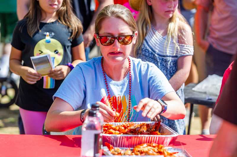 "PAMPLIN MEDIA GROUP: DIEGO DIAZ - Marisa Fanguy, aka, ""Cajun Sparkle"" digs into a foil pan of cooked crawfish Saturday.  Fanguy consumed 71/2 pounds of crawfish and was named the women's champion. This is the first year there was both a men's and women's champion division."