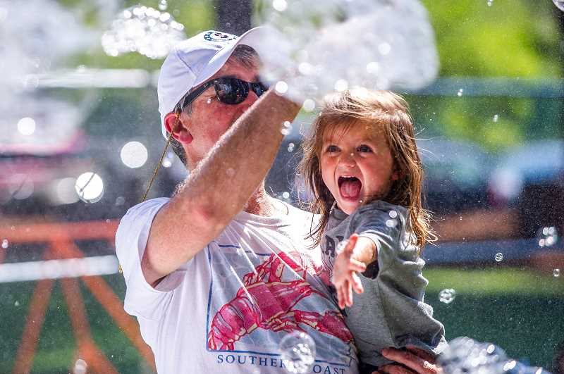 PAMPLIN MEDIA GROUP: DIEGO DIAZ - Dr. Paul Pumilia, who ultimately won the 2019 Tualatin Crawfish Festival crawfish-eating contest, and his daughter, share some fun moments with a bubble machine in Tualatin Community Park Saturday.
