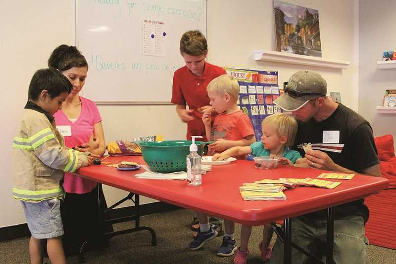 COURTESY PHOTO: TINA FOSTER  - Parents and their children explore learning activities during a Las Manitas Bilingual Preschool open house. The preschool, located inside the Mid-Valley Community Church in Woodburn is currently registering students for classes beginning Oct. 3., Woodburn Independent - News