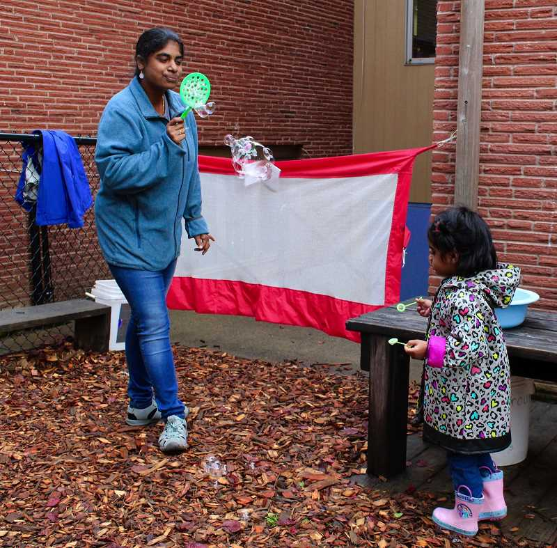 STAFF PHOTO: OLIVIA SINGER - A preschool student and her mother play with bubbles during a recess-like break on Thursday, Nov. 1.  , Hillsboro Tribune - News Hillsboro Parent Preschool + Kindergarten has been run entirely by parents for four decades. Hillsboro Co-Op school turns 40