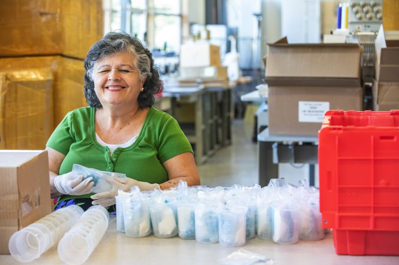TRIBUNE PHOTO: JONATHAN HOUSE - Marta Guzman helps put together science kits for Yellow Scope at Relay Resources.