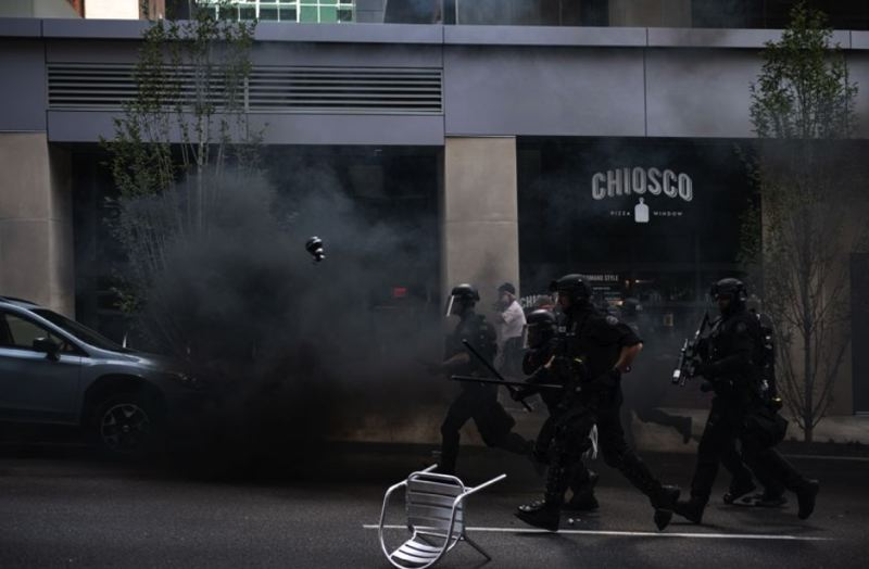 FILE PHOTO - Acrid smoke filled the air as Portland Police officers dressed in riot gear cleared Southwest Columbia Street on Aug. 4, 2018.