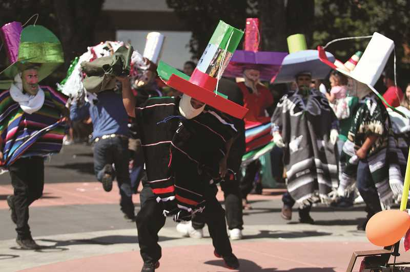 PMG PHOTOS: PHIL HAWKINS - Costumed performers dance and mingle with parade-goers on Saturday.