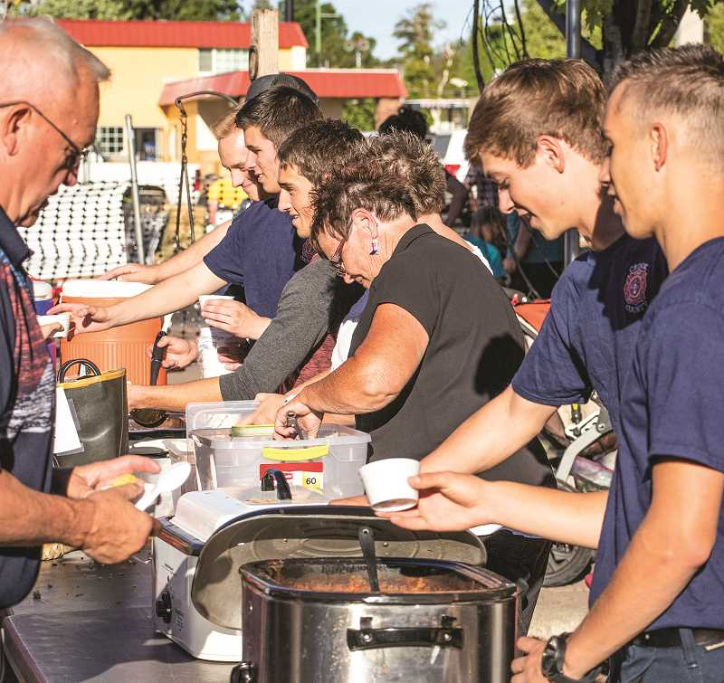 PHOTO COURTESY OF PRINEVILLE-CROOK COUNTY CHAMBER OF COMMERCE - Crook County Fire and Rescue employees and volunteers serve up chili at the Stampede Street Party during the Crooked River Roundup.