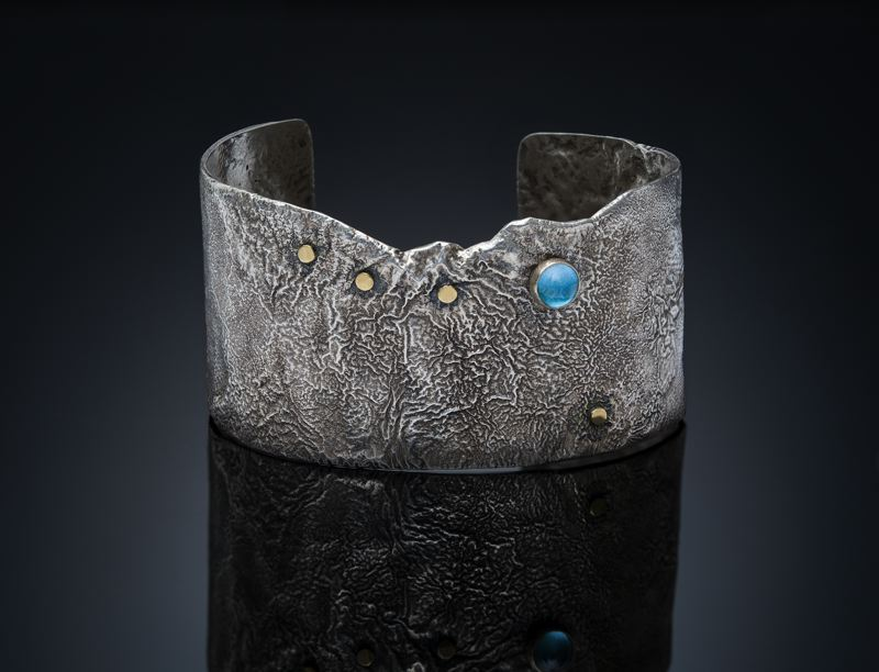 COURTESY PHOTO - Elisa Saucy is a jeweler who uses silver to give the impression of mountains, which she tops with semi-precious stones to depict moon and stars.