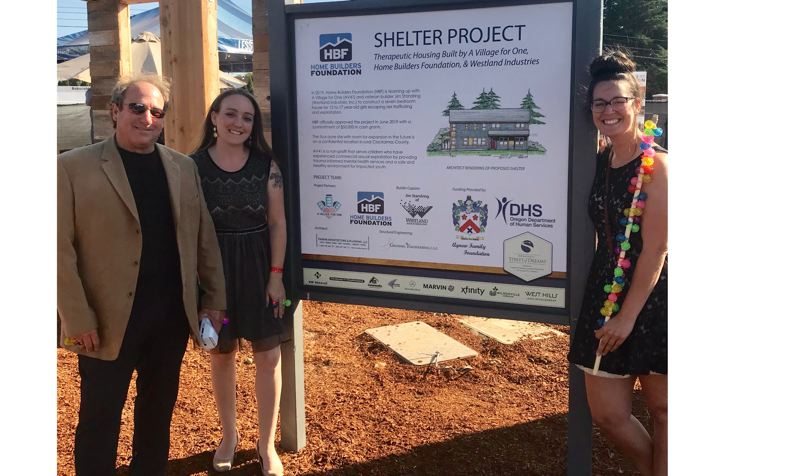 COURTESY PHOTO - FROM LEFT: A Village for One board president Mike Eichenberger, executive director and co-founder Cassie Trahan, and staff member Arielle Crist surround a sign highlighting the nonprofit's role as the philanthropic focus project of the year for the Home Builders Foundation.