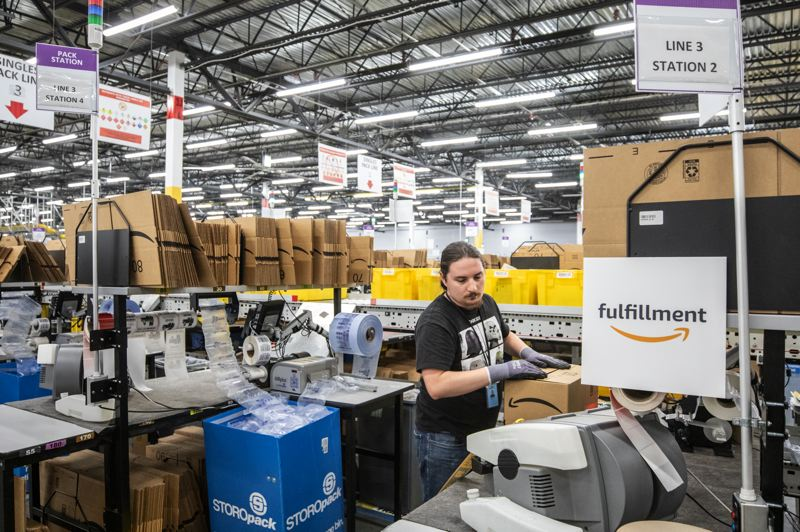 PMG PHOTO: JONATHAN HOUSE - Amazon employees box and pack orders at the Fulfillment Center in Troutdale.