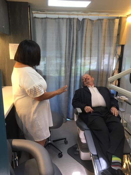 PMG PHOTO BY PETER WONG - Beaverton Mayor Denny Doyle tries out one of two medical/dental chairs in Virginia Garcia's new mobile clinic. At left is Serena Cruz, director of the Virginia Garcia Memorial Foundation, which raised $385,000 to pay for it.