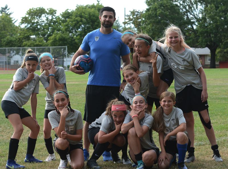 PMG PHOTO: DAVID BALL - Reynolds High graduate Justan Wolvert poses with one of his United PDX youth teams before a recent practice. He is the junior and Senior Academy Director with the club.