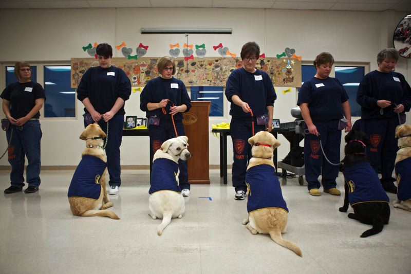 PMG FILE PHOTO - Inmates stand with dogs they helped train during a graduation at Coffee Creek Correctional Facility. Women at the prison talked about lives of abuse for a state study.