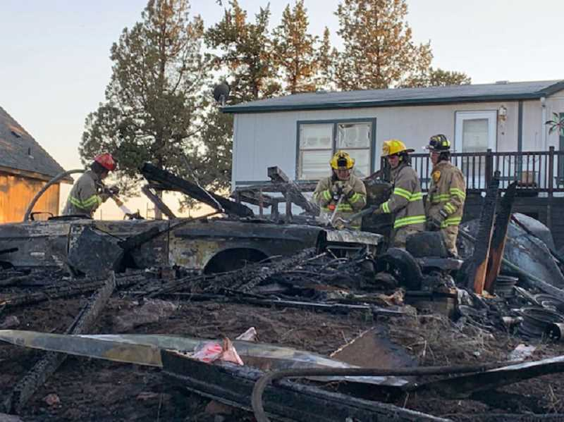 SUBMITTED PHOTO - Crooked River Ranch Fire and Rescue crews work the aftermath of a garage fire on the Ranch July 30. The blaze destroyed a detached garage and all of its contents, including three vehicles.