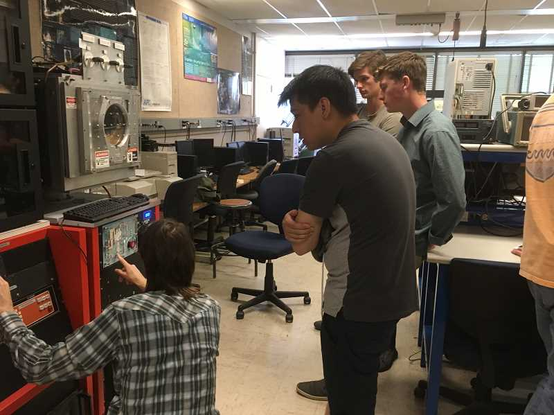 COURTESY PHOTO - PSU master's student Aaron Maroni shows PSU physics major Chuck Faber and Nathan Tidball, WHS 2019 graduate, and WHS senior Max Wilson how to operate and calibrate a sample coating machine.