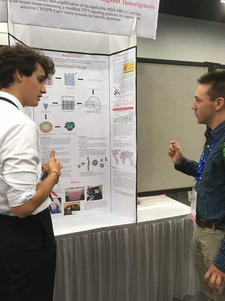 COURTESY PHOTO - WHS senior Jared Wieland presents his scientific research to PSU physics major Lewis Hicks.