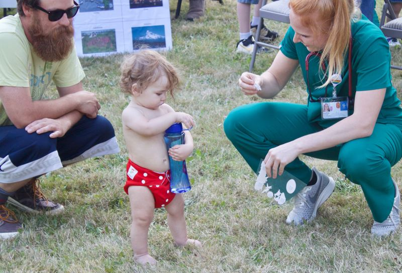 PMG PHOTO: CHRISTOPHER KEIZUR - Fourteen-month-old Charlie wasnt sure what to think about his sticker from Oregon Health & Science University during National Night Out.