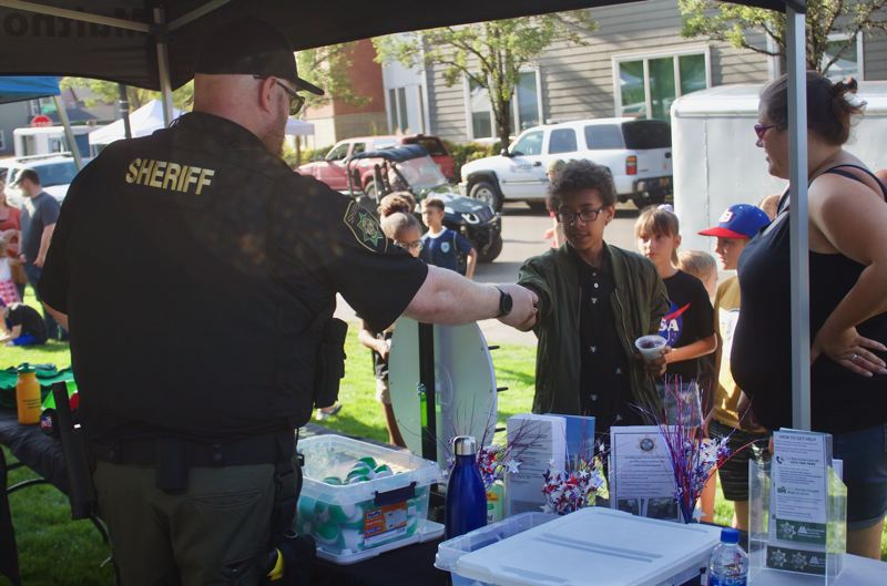 PMG PHOTO: CHRISTOPHER KEIZUR - Multnomah County Sheriffs Deputies handed out prizes during National Night Out Tuesday evening, Aug. 6.