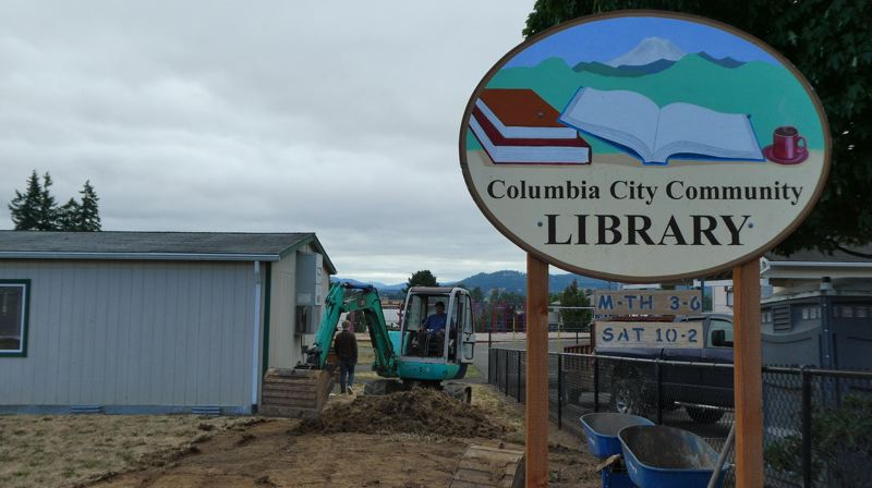 PHOTO COURTESY OF KIT GARDES - Contractors from Happy Hollow LLC work on installing a new sidewalk and walkway next to the Columbia City Community Library. The library is also slated to get new fencing and lighting. Together, the improvements are expected to allow the volunteer-run library to expand hours.