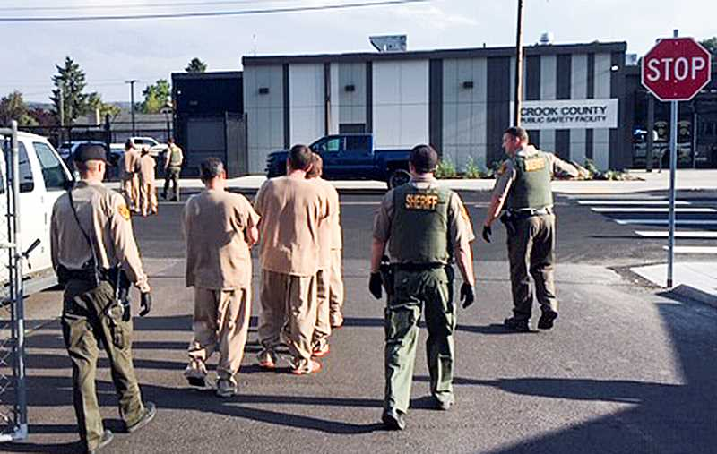 PHOTO COURTESY OF CROOK COUNTY SHERIFF'S OFFICE - Crook County law enforcement staff lead inmates from the old jail across the street to the new one on Monday evening.