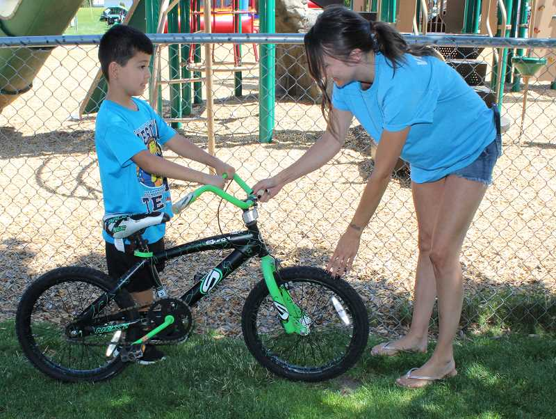 HOLLY M. GILL/MADRAS PIONEER - Ricardo Orozco, 7, was one of 11 lucky people who received a free bike at the event. Volunteer Amanda Norris, right, assists Ricardo with the bike.