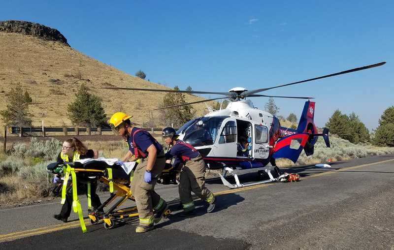 SUBMITTED PHOTO - Life Flight lands on U.S. Highway 97 Monday morning, responding to a collision between a dump truck and a motorcycle. The motorcyclist, who was pinned beneath the tires of the dump truck's trailer, was flown to St. Charles Bend, where he remained under intensive care Tuesday.