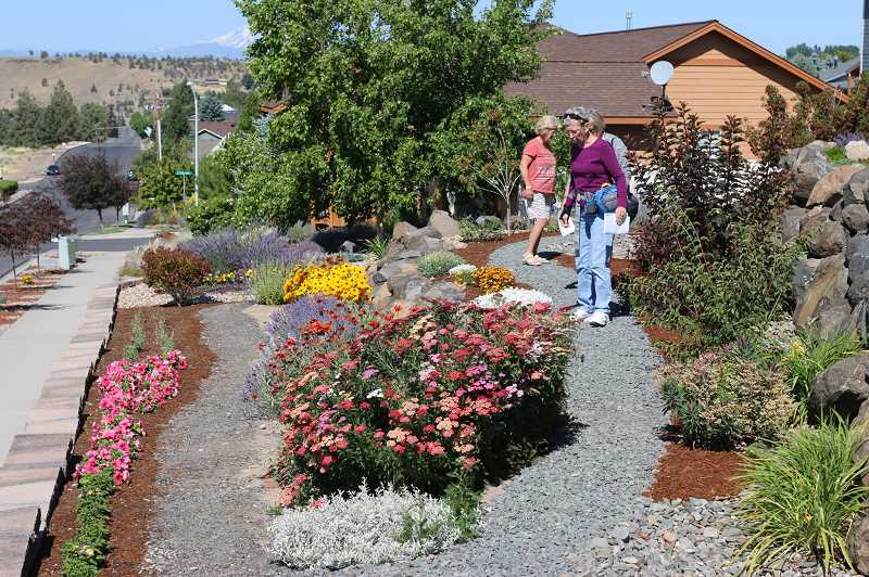 SUBMITTED PHOTO - Participants tour the garden of Joe and Cindy Stanfield, of Madras, during the High Desert Garden Tour's 26th annual event, which featured Jefferson County gardens.