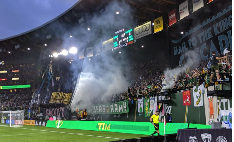 PAMPLIN MEDIA GROUP: JOSEPH GALLIVAN - The Timbers Army Evil Dead-themed tifo ahead of the Cascadia Cup home game against the Vancouver Whitecaps on August 10, 2019. Written on the chainsaw in blood was the old Woody Guthrie slogan that was written on his guitar, 'This machine kills fascists.' Unlike fans who went out of their way to wear the antifacist Iron Front three arrows symbol on their clothes after it was banned from flags and banners by MLS, this tifo avoided obvious controversy by not including the sign. The closest thing to three arrows were the Adidas ads around the field.
