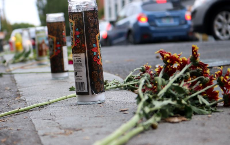 PMG PHOTO: ZANE SPARLING - Flowers and candles rest on a Portland street during a vigil.