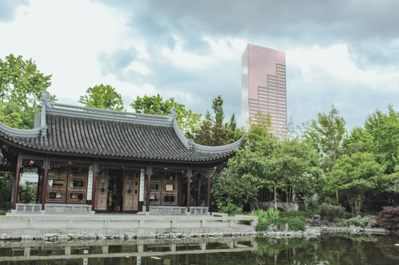 "PMG PHOTO: SAMANTHA KAR - While standing inside the Lan Su Chinese Garden, the 42-story U.S. Bancorp Tower, known as ""Big Pink,"" is fairly visible."