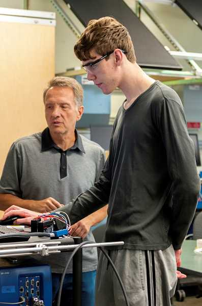 PMG PHOTO: CLARA HOWELL  - Oregon Tech professor Slobodan Petrovic, left, works with Wilsonville High School senior Russell Fitch during his engineering internship.