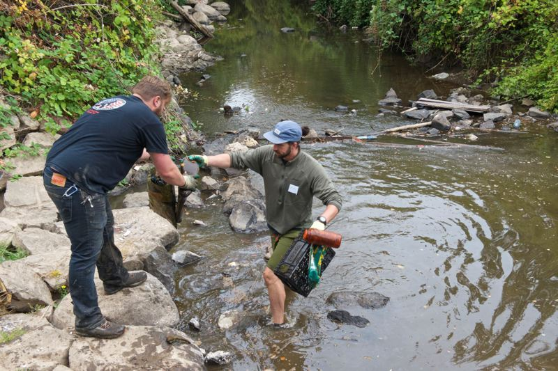 COURTESY PHOTO - A volunteer who walked in Johnson Creek hands his found objects to another volunteer on the bank.