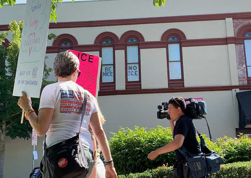 PMG PHOTO: GEOFF PURSINGER - A local sign against immigration officials hangs in  the windows outside the Washington County courthouse in downtown Hillsboro. The ACLU says ICE agents have regularly used the Hillsboro courthouse as a place to make arrests.