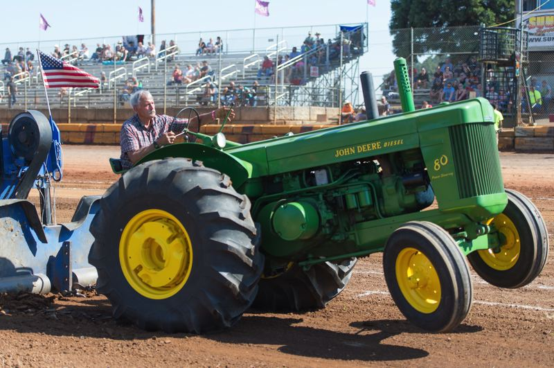 PMG PHOTO: CHRISTOPHER OERTELL - Ralph Puncochar of Hillsboro drives his John Deere tractor at Sunset Speedway during the 73rd Annual Banks BBQ.