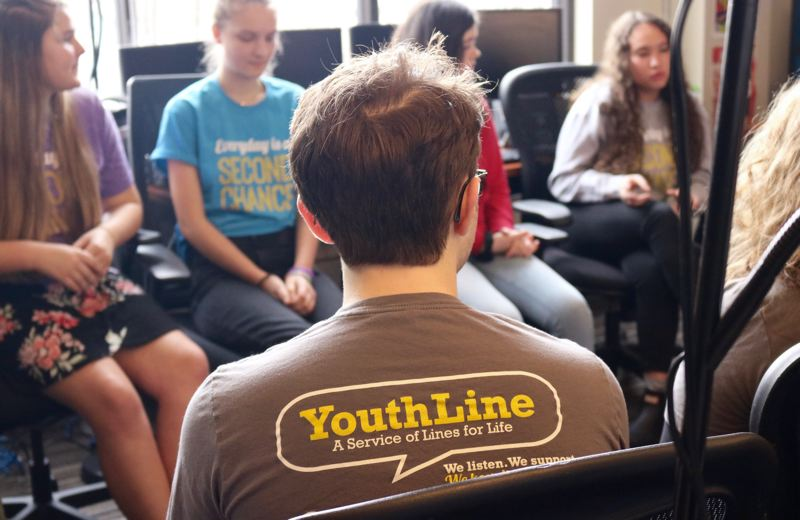 PMG PHOTO: ZANE SPARLING - Student volunteers at YouthLine share their experiences helping peers with mental health issues at the Lines for Life office on Friday, Feb. 15.