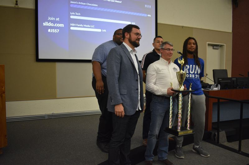 PMG PHOTO: SHANNON O. WELLS - Jason Jackson, center, accepts the first place trophy for his Pitch Fest presentation on Jasons Artisan Chocolates, surrounded by his fellow startup entrepreneurs and East Metro Economic Alliance Leaders at the Start-Up East Metro Pitch Fest at Gresham City Hall.