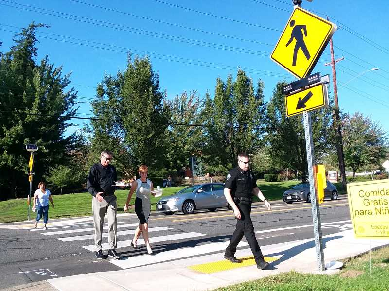 PMG PHOTO: RAY PITZ - City officials including, from front, Tualatin Police Chief Bill Steele, City Manager Sherilyn Lombos and Tualatin City Councilor Paul Morrison try out a pedestrian-activated signal on Sagert Street that connects a bus stop with Atfalati Park during a tour of traffic  bond improvements Monday evening.