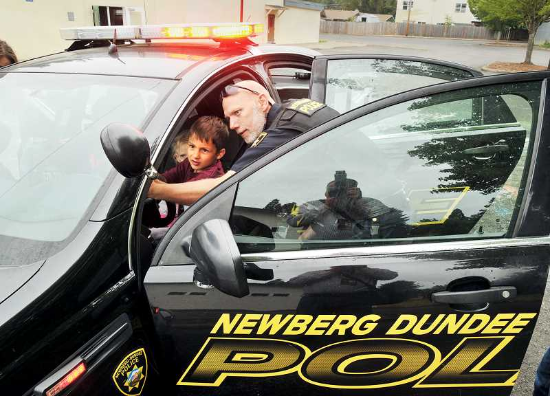 GRAPHIC PHOTO: GARY ALLEN - Officer Ken Howell of the Newberg-Dundee Police Department shows kids the interworkings of a police cruiser during Safety Town last week at the Chehalem Armory Center.