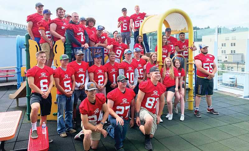 PHOTO COURTESY OF CROOK COUNTY HIGH SCHOOL HEAD FOOTBALL COACH, RYAN COCHRAN - The East team for the annual East West Shrine team poses for a photo in the play area at the Portland Shriners Hospital for Children. The team toured the facility a week prior to the East-West Shrine Game, which was held Saturday, Aug. 3 in Baker City. Former Crook County High School players Dominic Langley (No. 5 standing in the top center) and Caleb Parrott (No. 55 on the far right) both participated in the game.