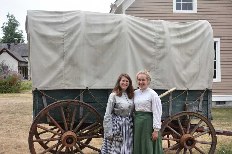 PMG PHOTO: EMILY LINDSTRAND - Jennifer Goldman, Philip Foster Farm programing director, and longtime volunteer, Molly Reel, stand in front of a covered wagon at the National Historic Site in Eagle Creek.