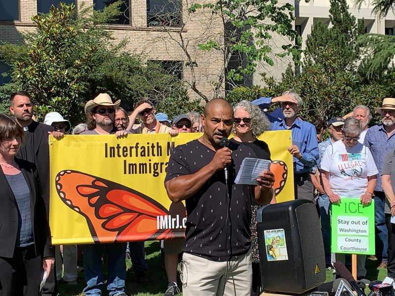 PMG PHOTO: GEOFF PURSINGER - Isidro Andrade Tafolla addresses a crowd of about 200 people outside the Washington County Courthouse in downtown Hillsboro on Monday, Aug. 12.