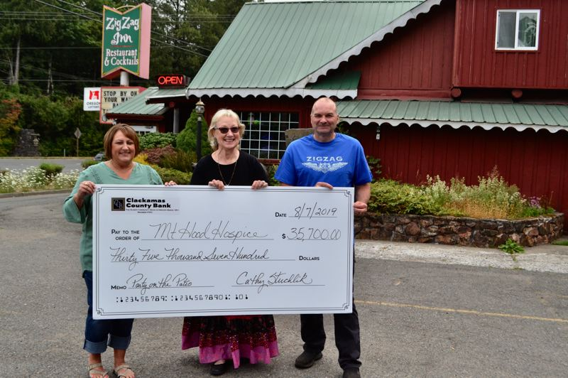PMG PHOTO: BRITTANY ALLEN - Mt. Hood Hospice Executive Director Rhonda Franke receives a 'big' check from Clackamas County Bank President Cathy Stuchlik with Zigzag Inn owner John Lazarides in attendance.