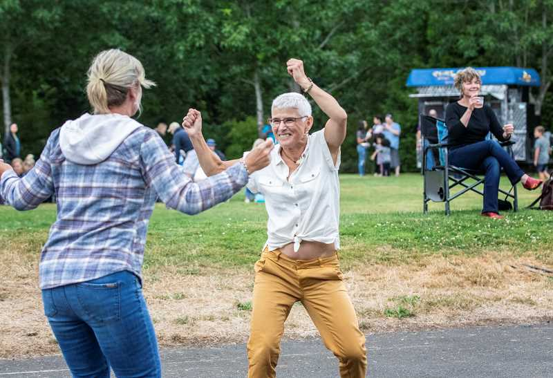 TIDINGS PHOTO: JONATHAN HOUSE - Deanie Parry, left and Michele Menard enjoy dancing to Stump City Sould at Music in the Park.