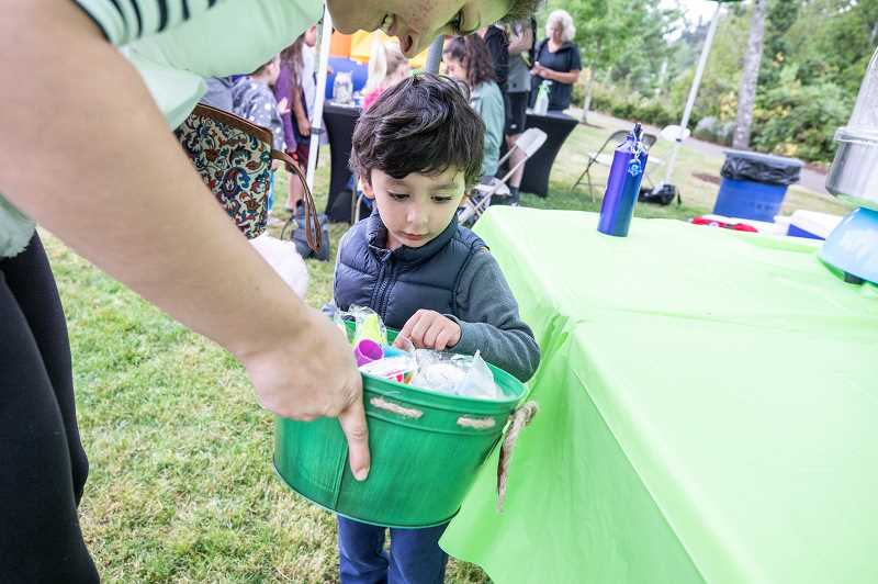 TIDINGS PHOTO: JONATHAN HOUSE - Soren Azad looks to grab a free toy during Music in the Park last week.