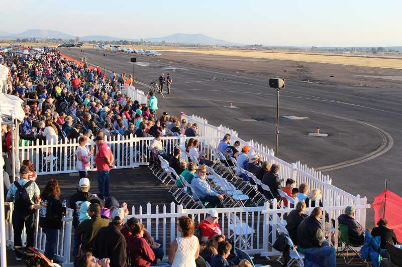 HOLLY M. GILL/MADRAS PIONEER - This year's Airshow of the Cascades will kick off Friday, Aug. 23, and run through Saturday, Aug. 24. Above, the Friday night crowd awaits the start of the aerobatics show at last year's event.