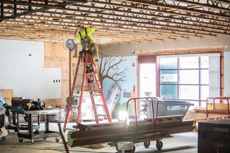 PMG PHOTO: JONATHAN HOUSE - A construction worker checks the measurements on the ceiling of the new makerspace at Westridge Elementary.