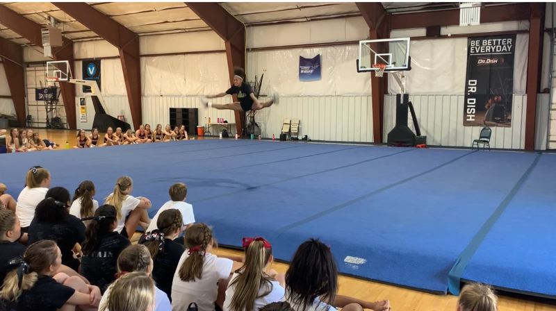 COURTESY PHOTO: SAVANNAH HOFFMANN - At a cheerleading camp in July at Blue River, St. Helens co-captain Savannah Hoffmann performs a move that helped her earn All-American honors.