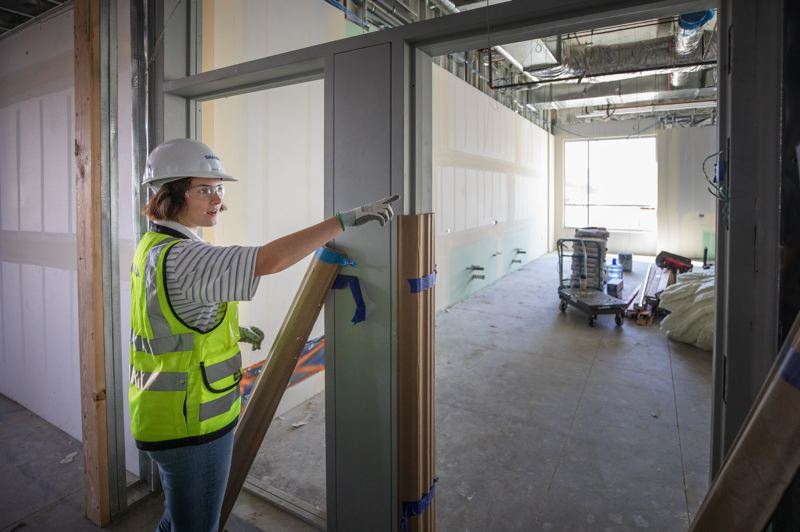TRIBUNE PHOTO: JONATHAN HOUSE - Grace Gary, a Sherwood High School student who spent the summer as an intern with Skanska, talks about one of the classrooms in the new Sherwood High School.