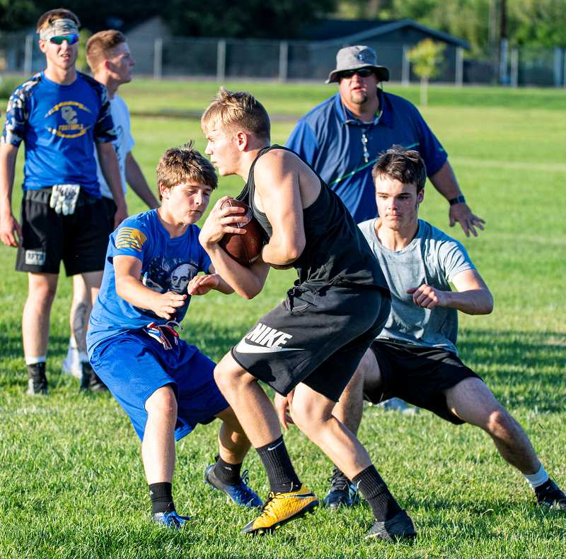 LON AUSTIN/CENTRAL OREGONIAN - A runner tries to evade a pair of defensive players as the Cowboys worked on gang tackling technique Tuesday night during the Pigskin Football Camp. Head coach Ryan Cochran, who is in the background, says the camp is essential to get ready for the season.
