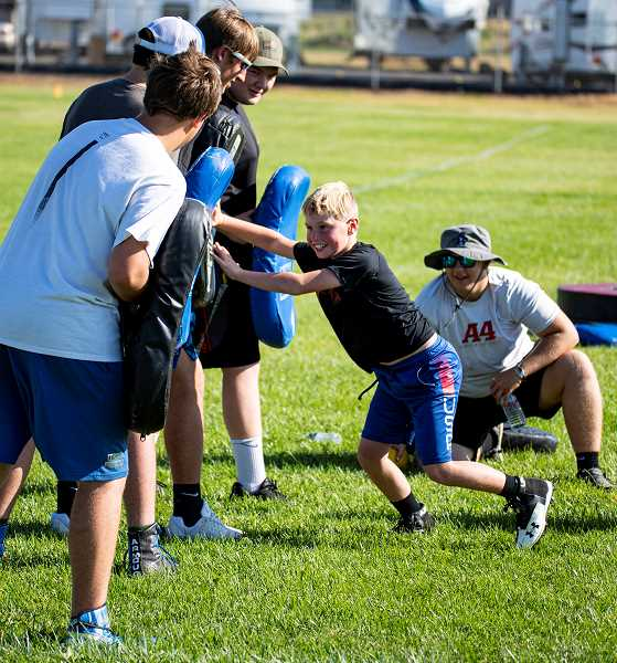 LON AUSTIN/CENTRAL OREGONIAN - A grade school football player works on blocking technique under the supervision of several members of the CCHS football team. The annual four-day Cowboy Pigskin Football Camp finished on Thursday evening.
