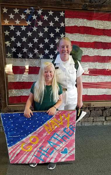 SUBMITTED PHOTO - Heather Ptomey, right, is joined by her younger sister, Ilsa Ptomey, with the 'Go Navy' picture she made, at the end of the three-week Naval Base Camp Heather took part in.